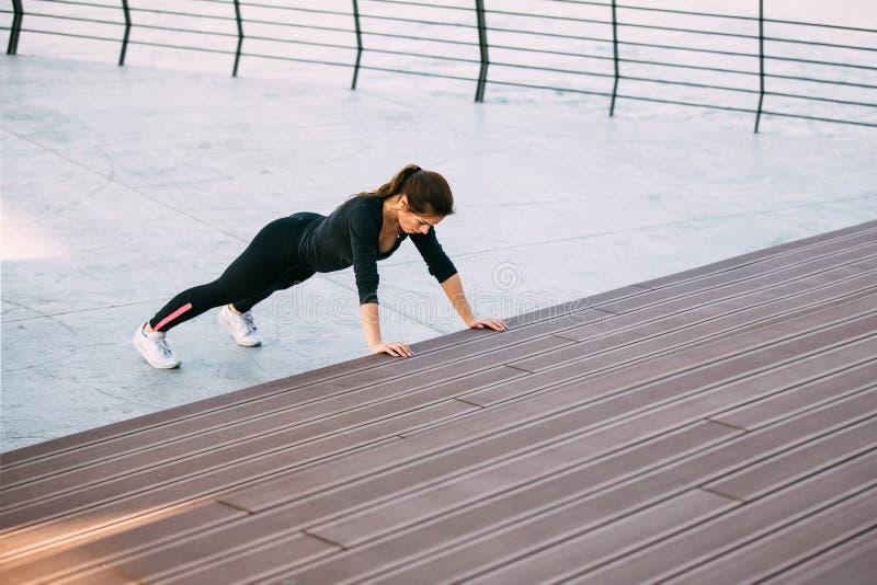 Push ups. Beautiful fitness woman doing push ups during outdoor training workout stock photo
