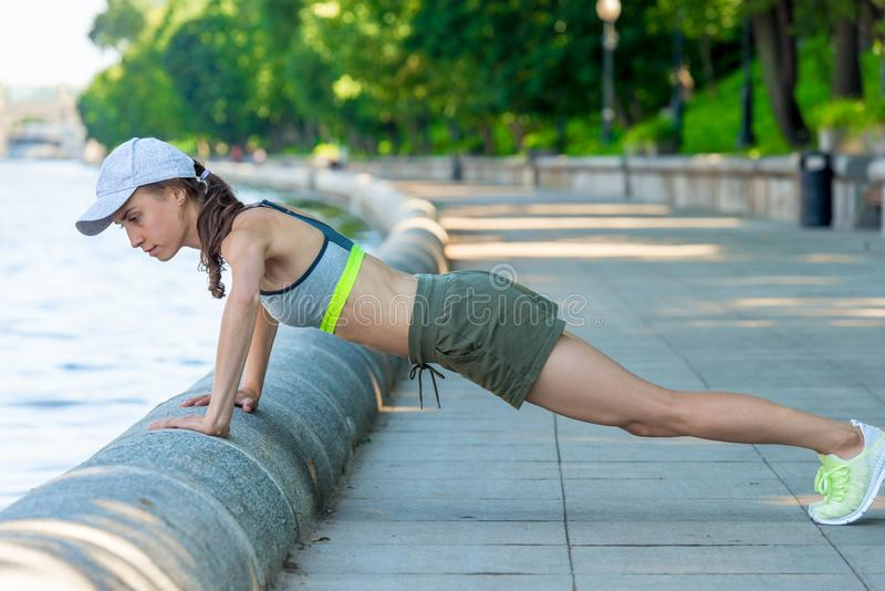 push-ups on the city promenade, active woman with a sports figure during royalty free stock photo
