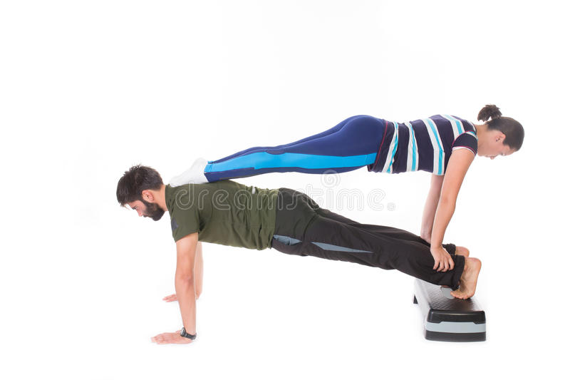 Push-ups. Fit couple doing push-ups one on the other's back - isolated on white royalty free stock photos