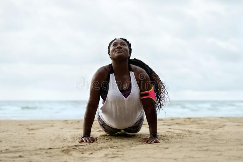 Push-ups fitness african woman doing pushups outside on beach. stock photo