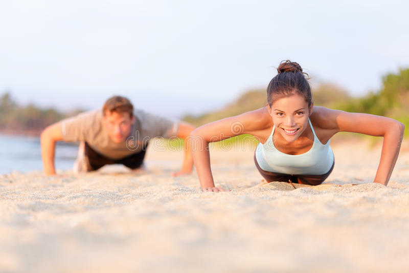 Push-ups fitness people working out on beach royalty free stock images