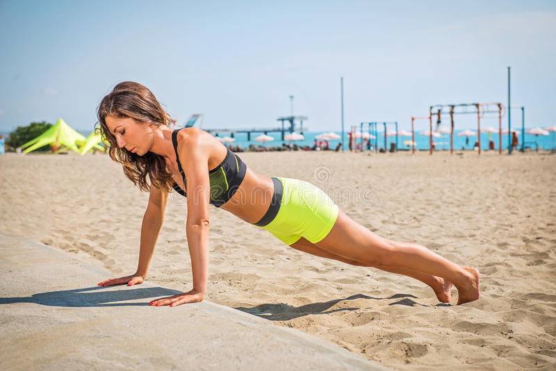 Push-ups fitness woman doing pushups outside on beach. Fit female sport model girl training crossfit outdoors. royalty free stock image