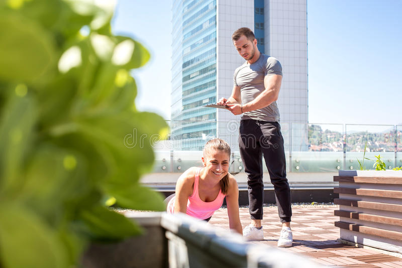 Push ups outdoor with personal trainer support. Personal trainer support and motivate his client while doing push ups outdoor royalty free stock photo