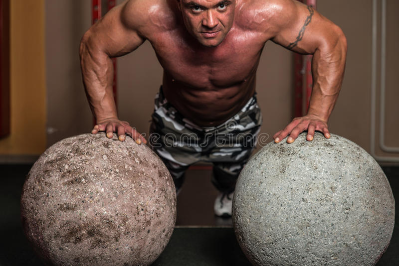 Push ups. Portrait Of A Bodybuilder, Young Man Doing Push Ups Exercise Against Round Stone royalty free stock photography