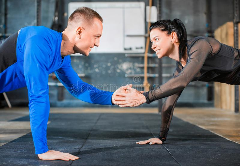 Push-ups together. Healthy couple in gym, workout with own body weight. Close ip photo. Active and sporty lifestyle concept stock image