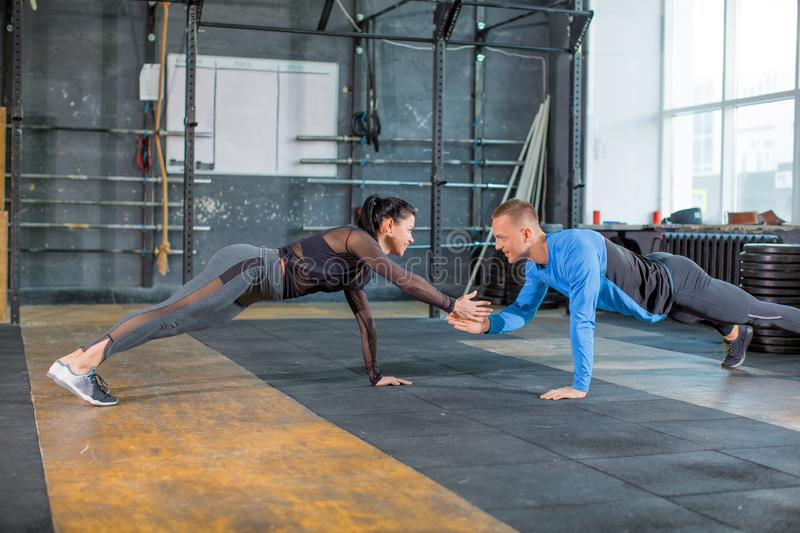 Push-ups together. Healthy couple in gym, workout with own body weight. Active and sporty lifestyle concept stock images