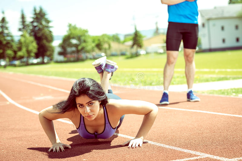 Push-ups with trainer outdoor. Young female doing push ups exercise outdoor on athletics sport track during hot summer day with help of her personal trainer royalty free stock photo
