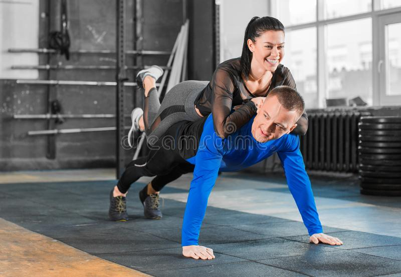 Push-ups with woman on back. Healthy couple in gym, workout with own body weight. Push-ups with women on back. Healthy couple in gym, workout with own body royalty free stock photo