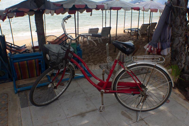 Pushbike rosso vicino agli ombrelli di spiaggia fotografia stock libera da diritti
