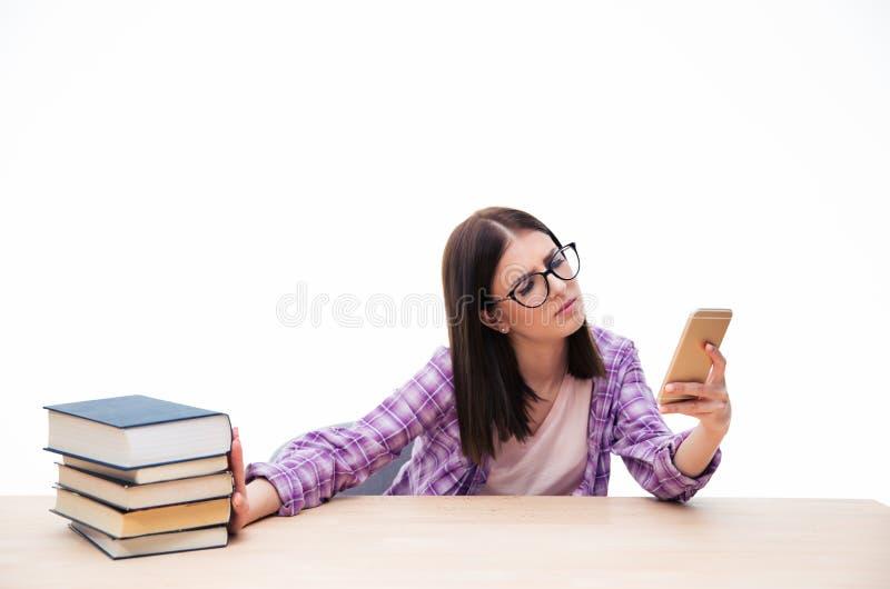 Pushen för den kvinnliga studenten ut bokar och genom att använda smartphonen royaltyfria foton