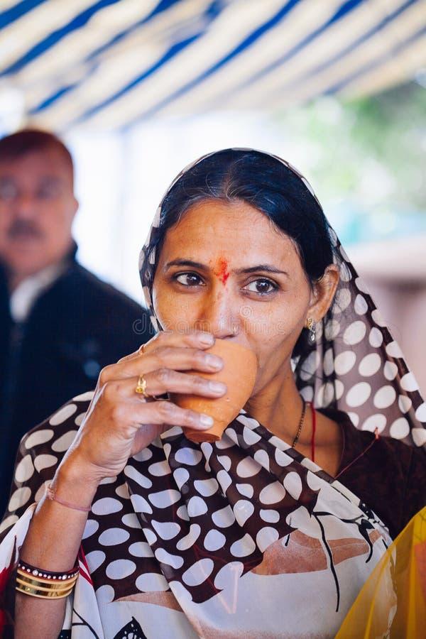 PUSHKAR, ÍNDIA - 16 de janeiro de 2017 chá bebendo do masala da mulher no s fotos de stock royalty free