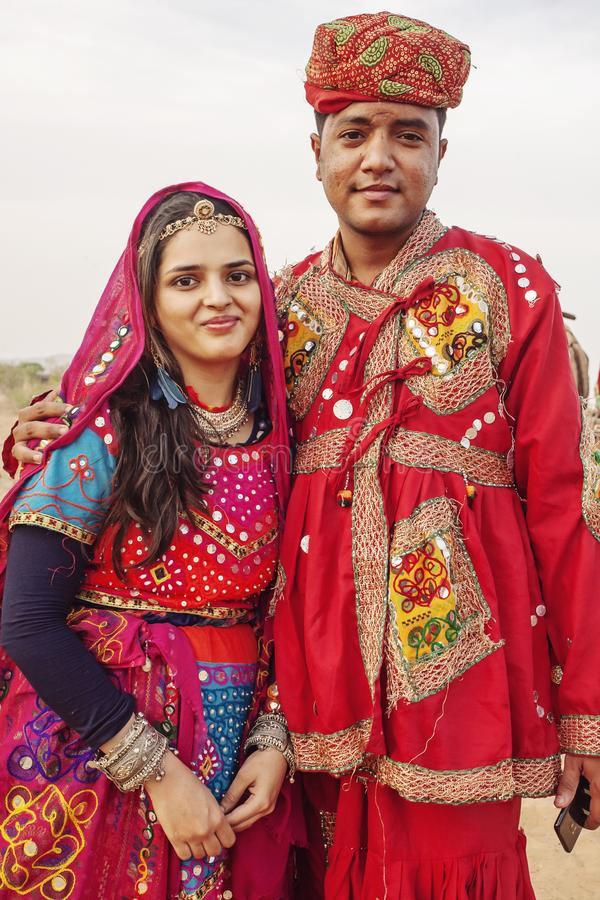 Traditinally dressed young Indian couple with camels and vehicle at Pushkar desert royalty free stock photos