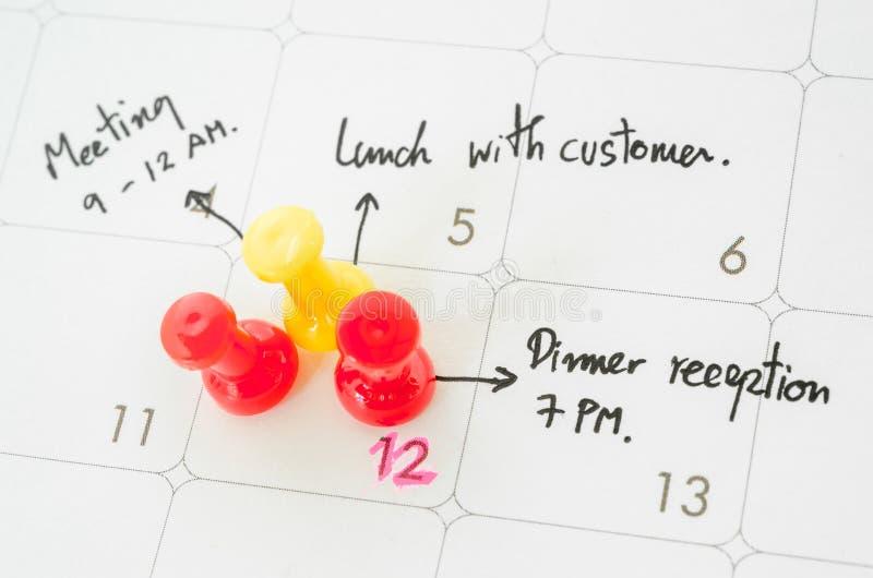 Pushpin на календаре с занятым днем стоковое фото