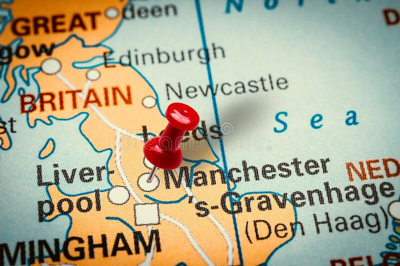 Pushpin pointing at Manchester city in United Kingdom. PRAGUE, CZECH REPUBLIC - JANUARY 12, 2019: Red thumbtack in a map. Pushpin pointing at Manchester city in stock photo