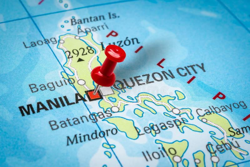 Pushpin pointing at Manila city in Philippines. PRAGUE, CZECH REPUBLIC - OCTOBER 28, 2019: Red thumbtack in a map. Pushpin pointing at Manila city in Philippines royalty free stock photo