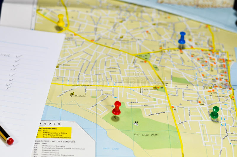 Pushpins and list on map stock photography