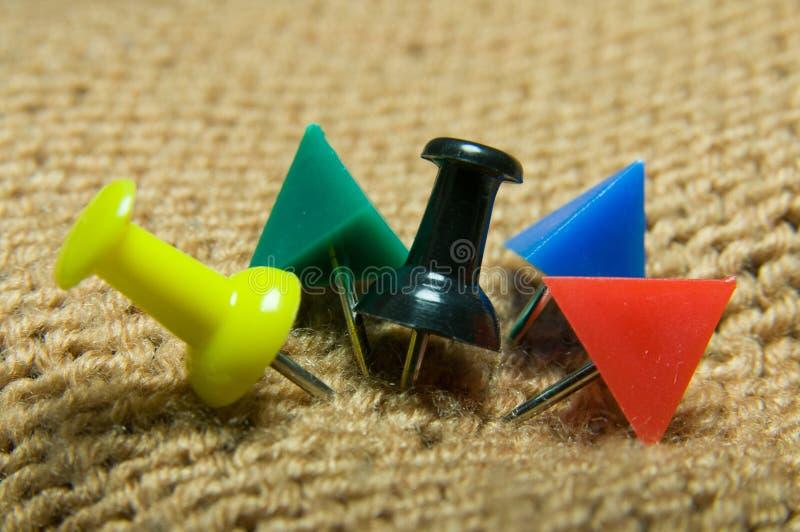 Pushpins na beż trykotowej tkaninie obrazy stock