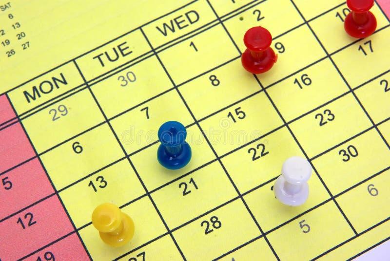 Pushpins no calendário fotografia de stock royalty free