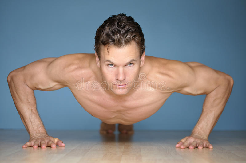 Pushup. Handsome muscular man looks at camera while performing pushup on floor with blue wall background royalty free stock photography