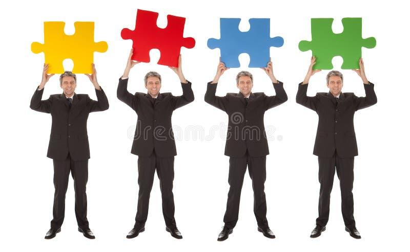 pussel för folk för jigsaw för holding för affärsgrupp royaltyfri foto