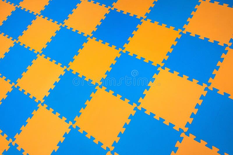 Pussel för gummiapelsin-blått kulört golv arkivbilder