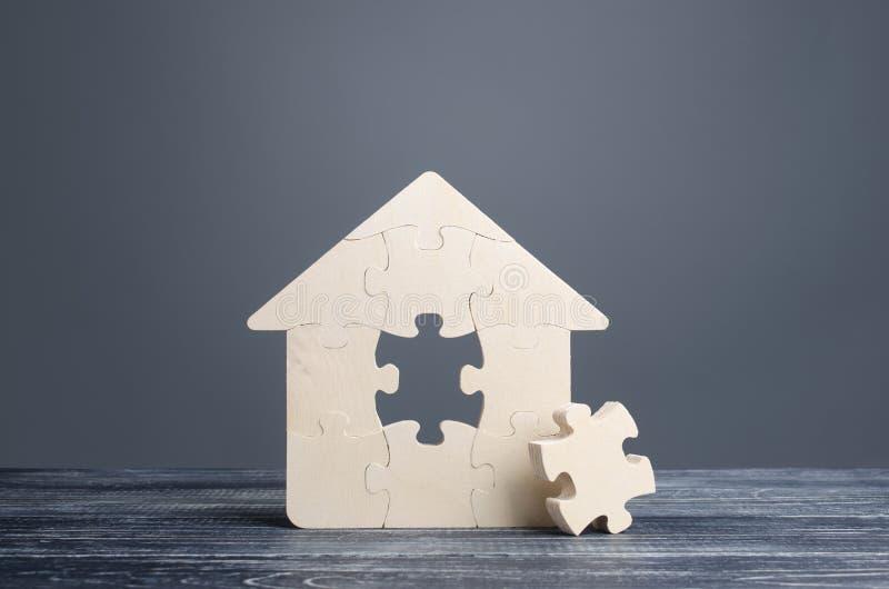 Pussel-hus med en bit som saknas Förvärvet eller byggandet av en bekväm dröm hem Inköpsfastighet för hypotekslån royaltyfri bild