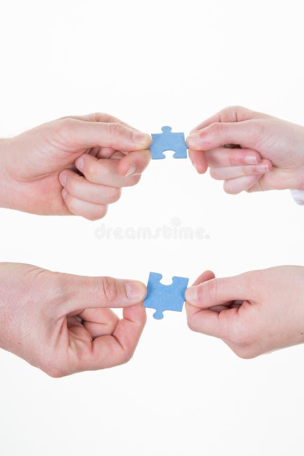 Pusslet för teamworkgrupp människorinnehavet lappar fyra händer på vit royaltyfria bilder