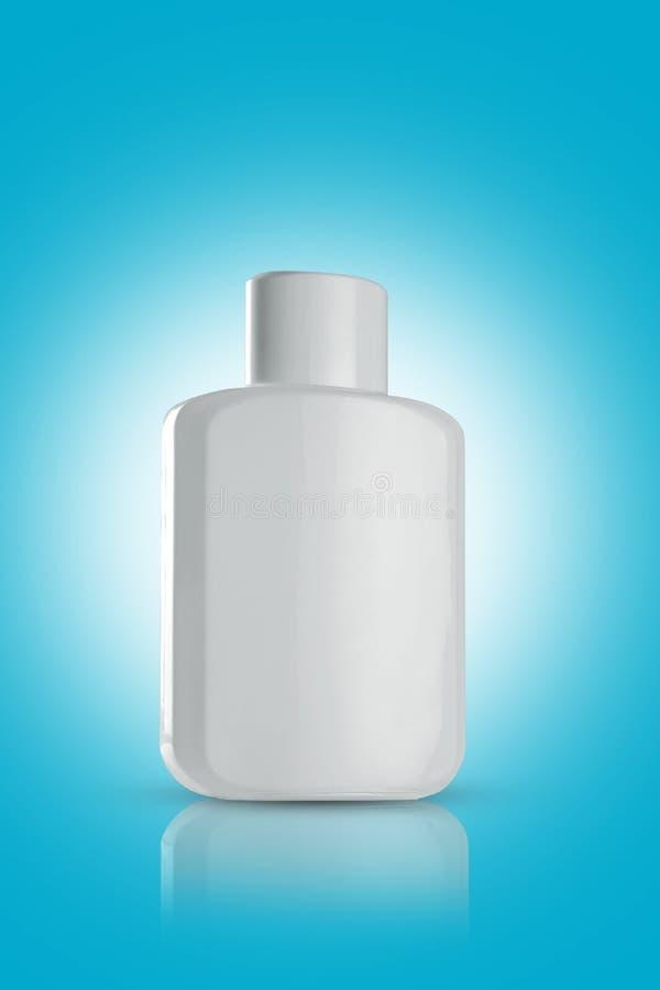 Pusta biała buteleczka perfum na niebieskim tle obrazy royalty free