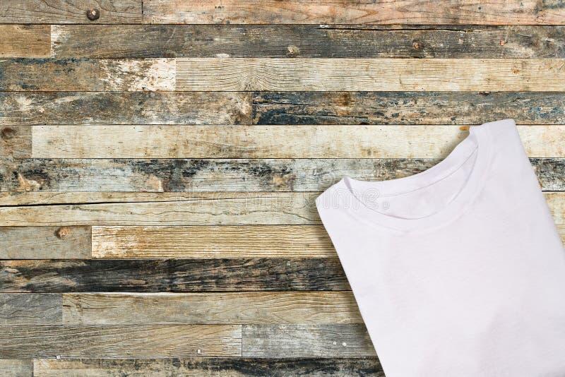 Pusta biała fałdowa koszulka na drewnianym tle fotografia stock