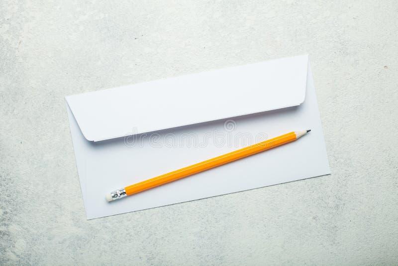 Pusta biała koperta i ołówek na białym rocznika biurku zdjęcie stock