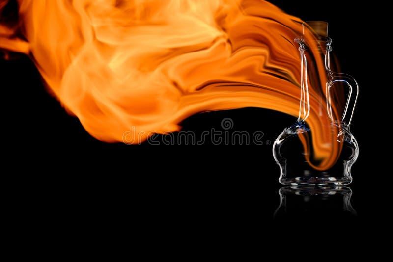 Pusta butelka dla oleju lub octu w pożarniczych płomieniach obrazy royalty free