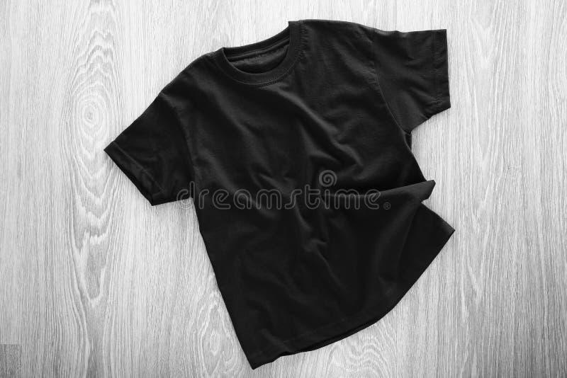 Pusta czarna koszulka na drewnianym tle zdjęcie stock