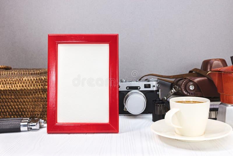 Pusta czerwona fotografii rama, filiżanka kawy i klasyk kamera z starym, obraz stock
