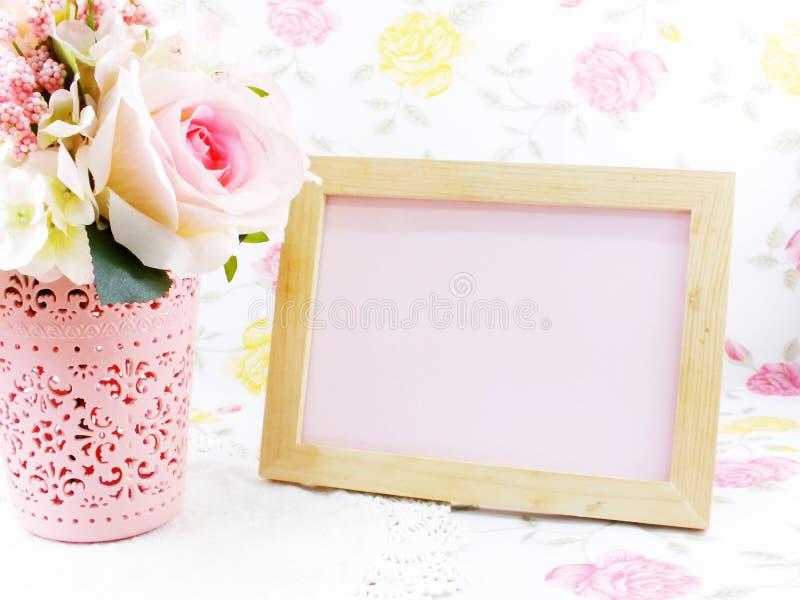 Pusta drewniana fotografii rama, róże i kwitniemy na stole obraz royalty free