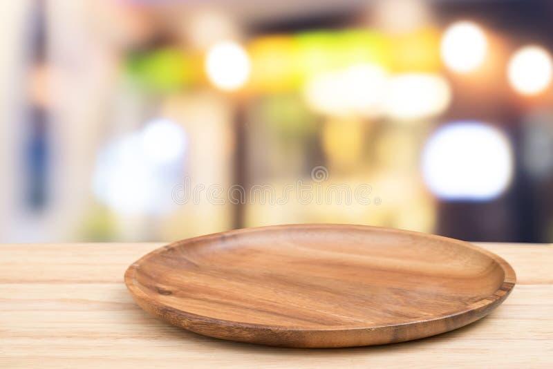 Pusta drewniana taca na perspektywicznym drewnianym stole na wierzchołku nad blurco fotografia royalty free