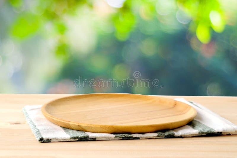 Pusta drewniana taca na stole nad plamy zieleni parka tłem, jedzenie zdjęcia royalty free
