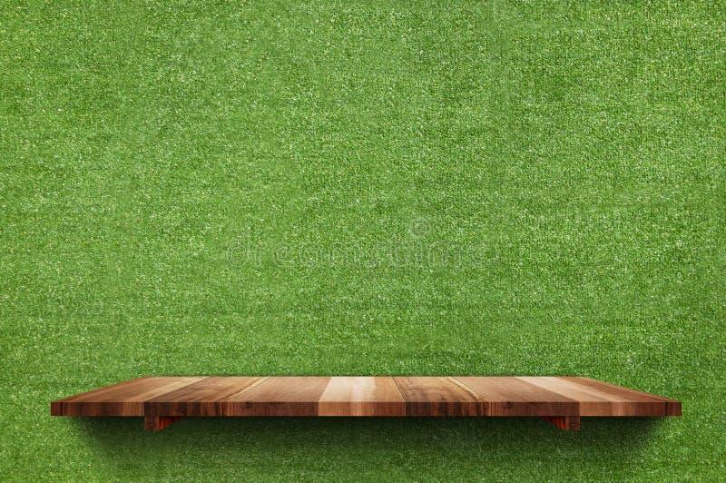 Pusta drewno deski półka przy sfałszowanym zielonej trawy ściany tłem, egzamin próbny fotografia stock