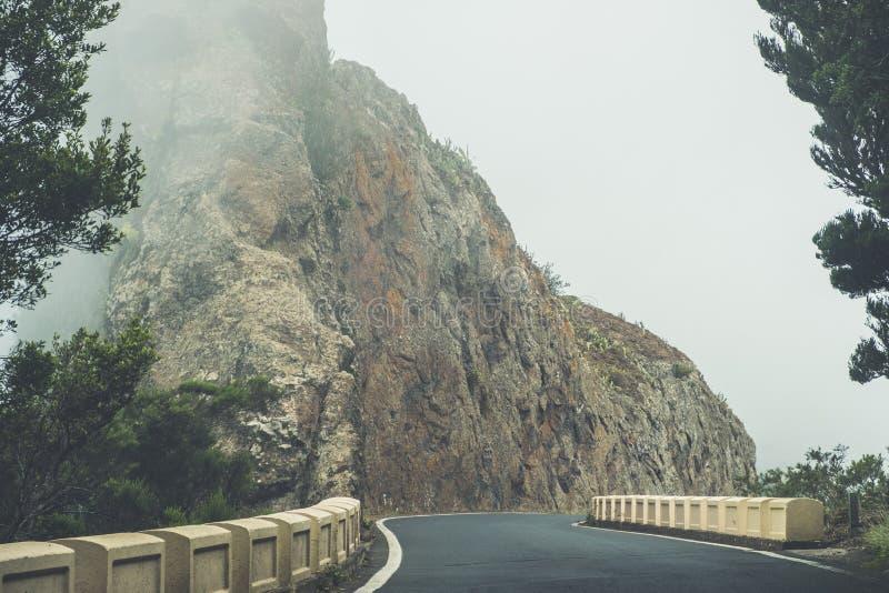 Pusta droga w gęstej mgle w góra krajobrazie - obraz royalty free