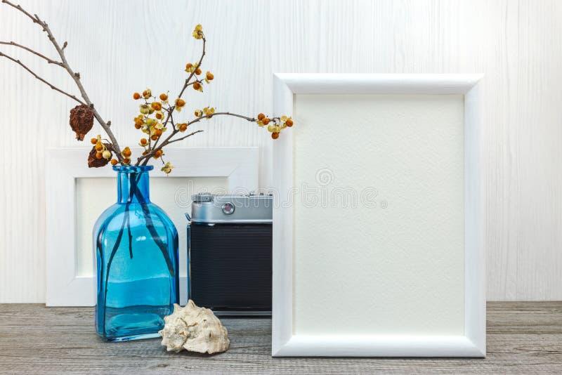 Pusta fotografii rama z błękitną szklaną wazą i seashell na drewnianych półdupkach obraz stock