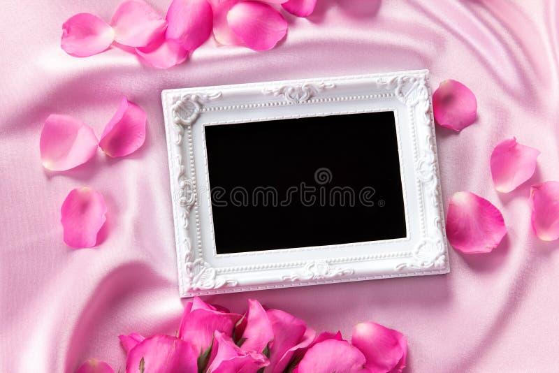 Pusta fotografii rama z bukieta cukierki menchii róż płatkiem na sof fotografia stock