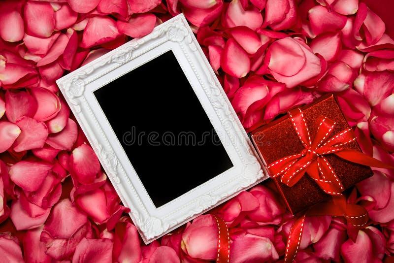 Pusta fotografii rama z cukierki menchii róż płatka i czerwień prezenta pudełkiem zdjęcie stock