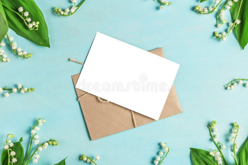 Pusta kartka z pozdrowieniami w ramie leluja dolina kwitnie na pastel barwiącym błękitnym tle Mieszkanie nieatutowy Odg?rny widok obrazy stock