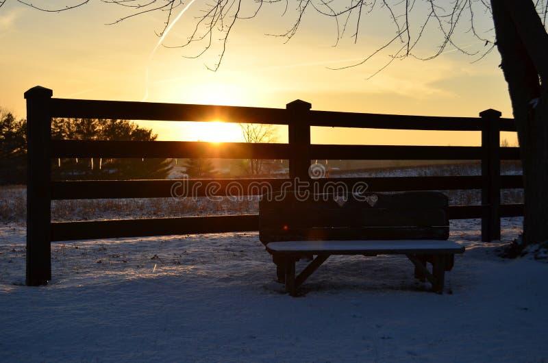 Pusta kochanek ławka na zimnym śnieżnym ranku obraz stock