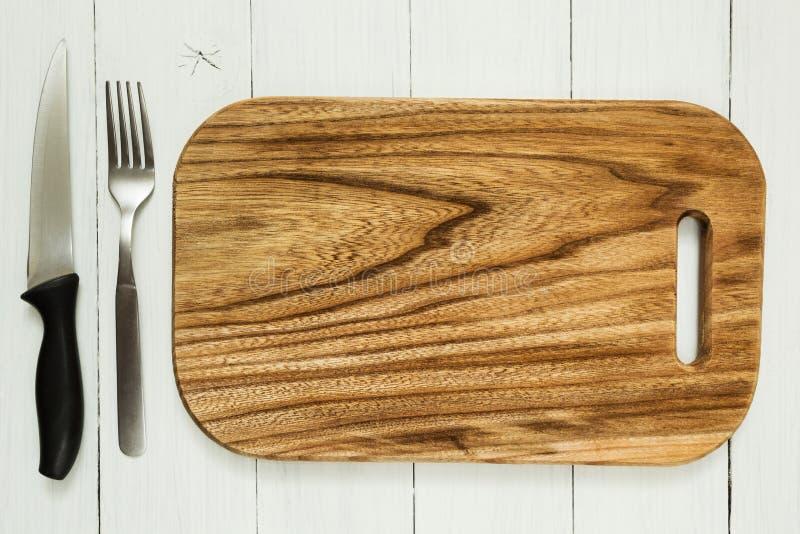 Pusta kuchni deska z nożem i rozwidlenie na białym drewnianym stole Opróżnia przestrzeń fotografia stock