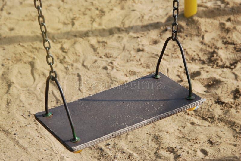 Pusta metalu łańcuchu huśtawka w boisko piaska tle rocznika filtr zdjęcie stock