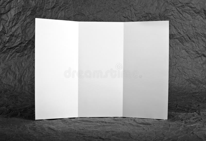 Pusta nadokienna fałd ulotka przy popielatym marszczącym papierowym tłem obraz stock