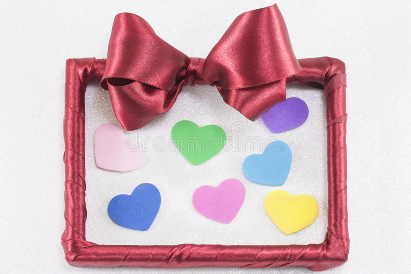 Pusta obrazek rama z czerwonym faborkiem z kolorowymi sercami obrazy stock