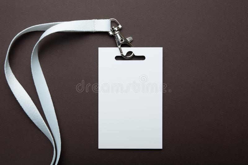 Pusta pusta odznaki karta identyfikacyjna z białym neckband odizolowywającym na brązu tle, przestrzeń dla teksta obraz stock