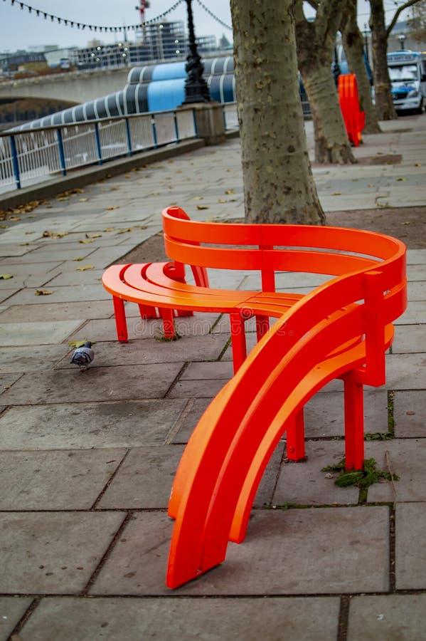Pusta pomara?czowa ?awka na rzecznym Thames London na po?udnie deponuje pieni?dze obrazy royalty free
