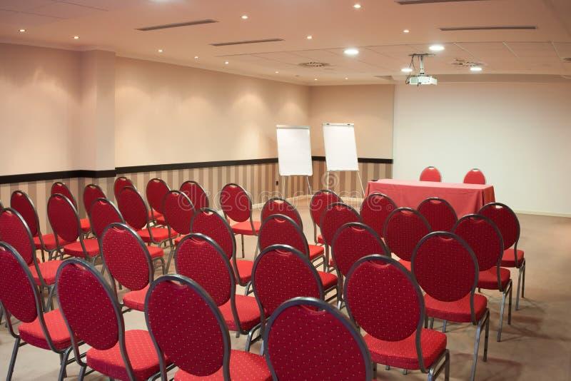 Pusta sala konferencyjna z czerwonymi krzesłami zdjęcia stock